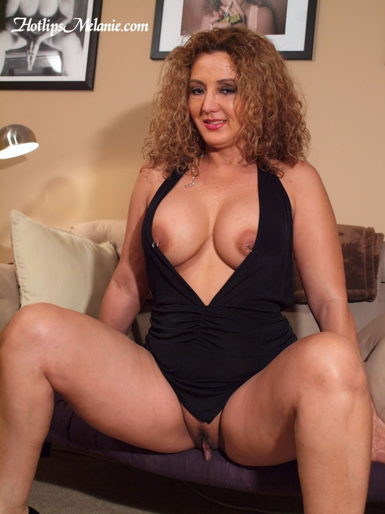 Hotlips Melanie spread her legs and large labia with her big tits popping out of her tight dress.