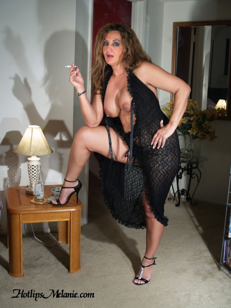 Hotlips Melanie puffing on a cigarette in lingerie and high heels. Her big tits and pierced nipples exposed.
