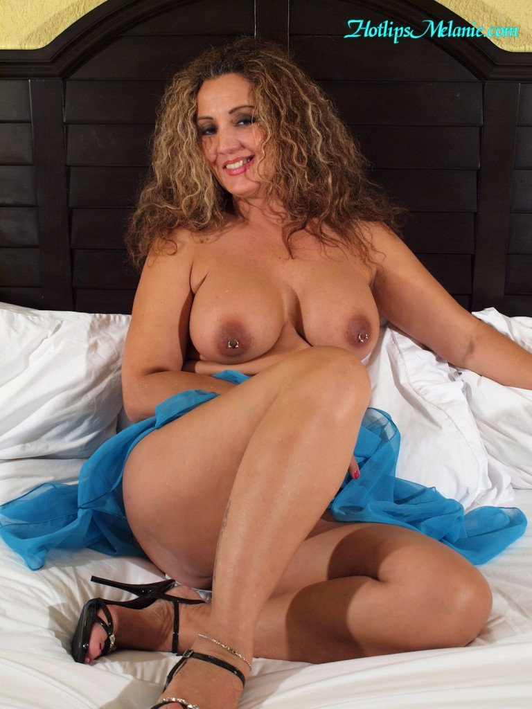 Hotlips Melanie, the Latina Milf, is nude in her bed wearing only high heels.