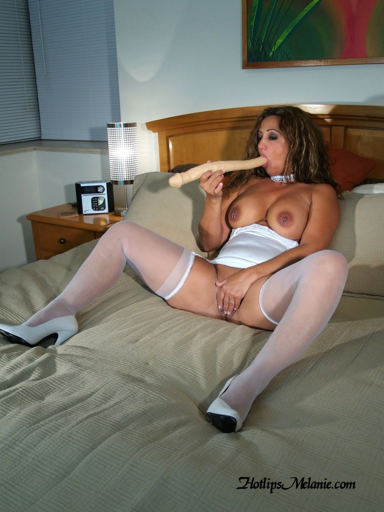 Hotlips Melanie sucks a big dildo cock with her stocking clad, high heeled legs spread.