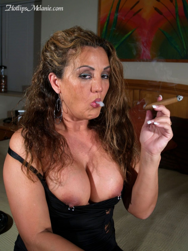 Big tits Hotlips Melanie is doing a puff and blow on her cigar. Her big tits are popping out.