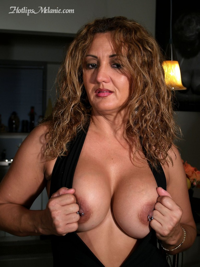Hotlips Melanie, the big tit Latina Colombian milf exposes her deep cleavage.