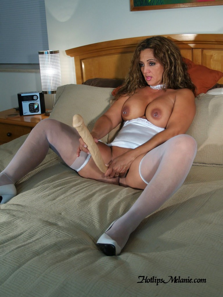 Hotlips Melanie, high heeled legs spread wide, fucks herself with her big double headed dildo.