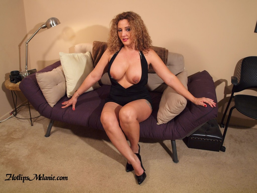Big tit, high heeled Latina Milf, exposes her big tits and pierced nipples in a short skirt.