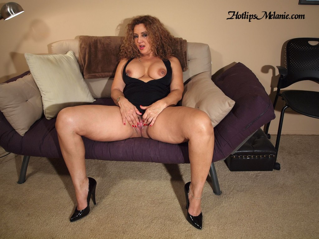 Latina milf spreads her high heeled, sexy legs, and large labia with her big tits, and pierced nipples exposed.