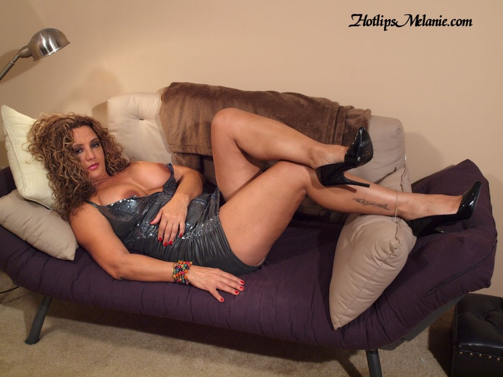 Hotlips Melanie, the sexy leg, high heeled, big tit Latina Milf porn star shows of her  legs on a short skirt.
