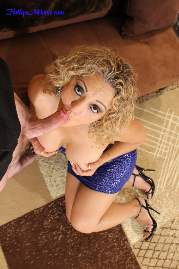 Glamorous pornstar, Hotlips, Melanie, is on her knees giving a blowjob.