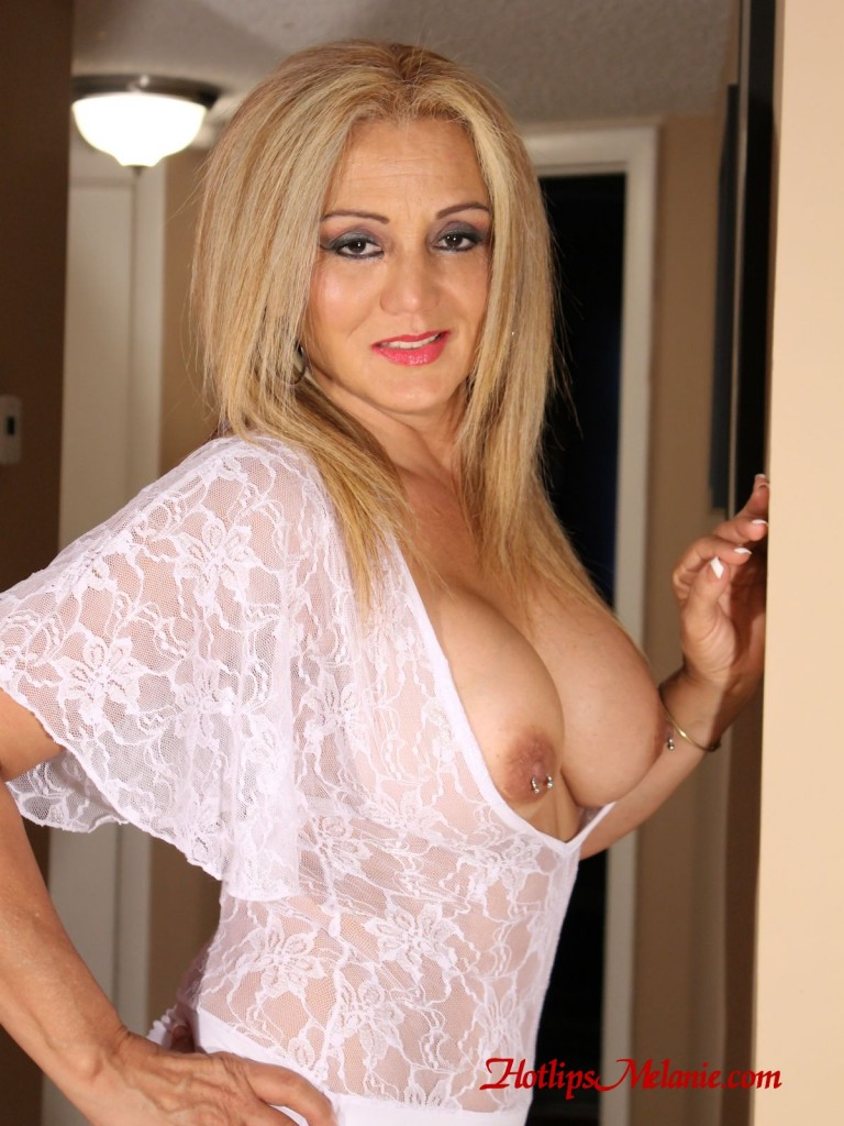 Hotlips Melanie exposes her big tits and pierced nipples in a glamour photo.