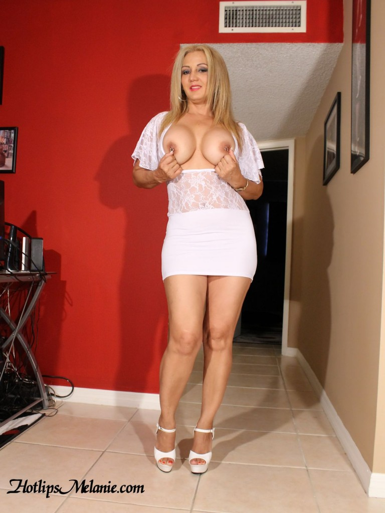 Big tit blonde Latina Milf in a short skirt and high heels showing off her sexy legs.