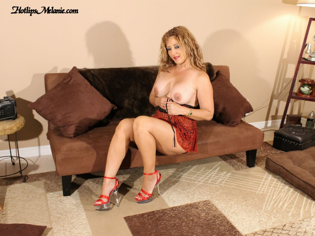 Hotlips Melanie in a mini skirt and topless showing off her sexy high heeled legs and big boobs.