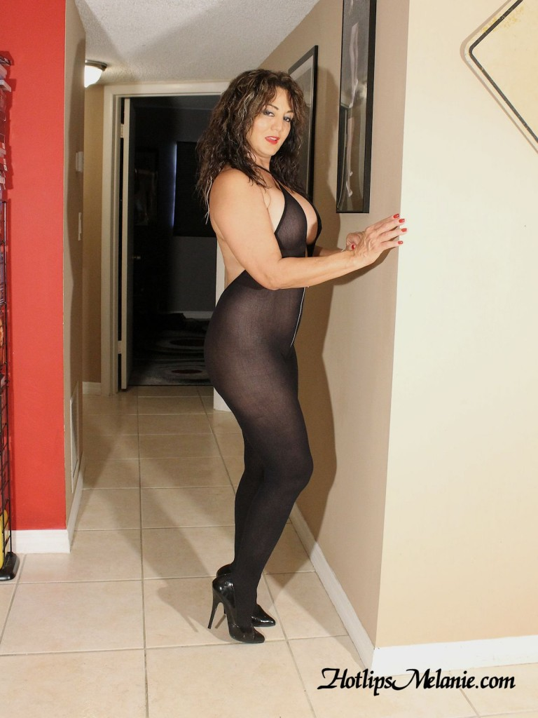 Brunette, Hotlips Melanie in a body stocking and high heels.