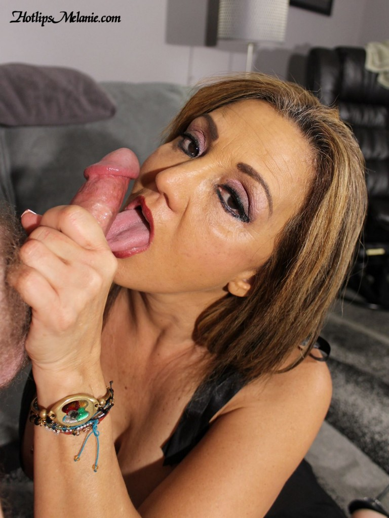 Hotlips Melanie is on her knees licking a big cock.