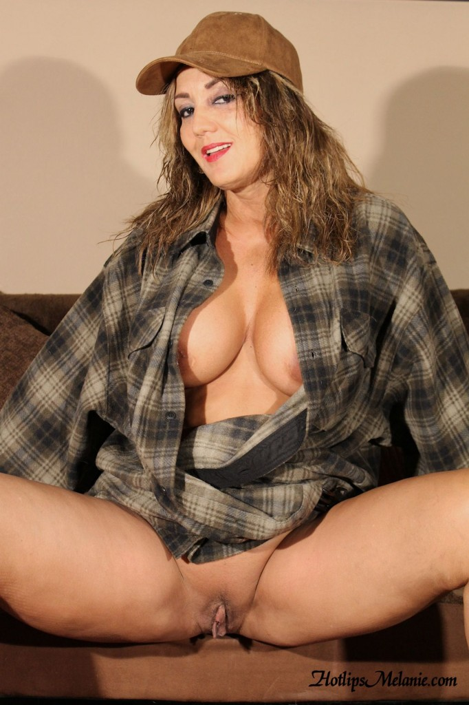 Big tit country girl spreads her legs to reveal her large labia.